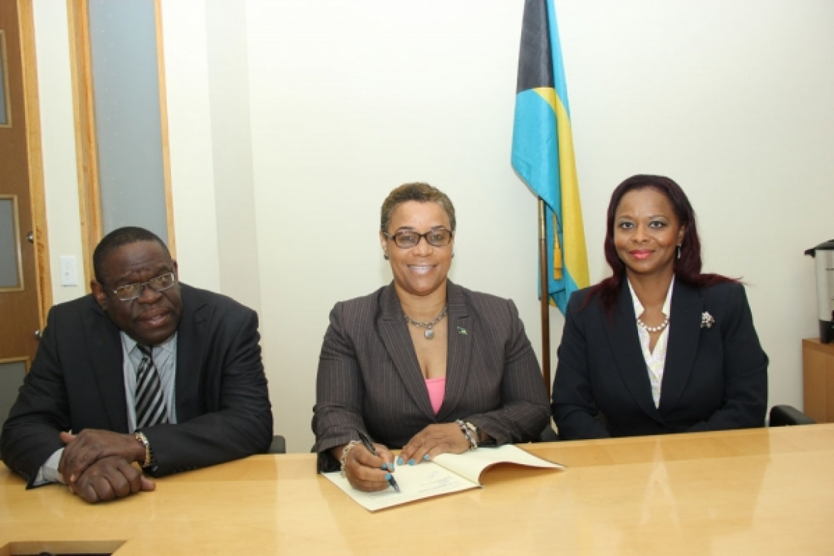 Bahamas Minister of Financial Services, Hon. C. V. Hope Strachan (centre) signing the MOU, while Permanent Secretary, Mr. David Davis and Director of The Bahamas Bureau of Standards and Quality, Dr. Renae Ferguson-Bufford look on.